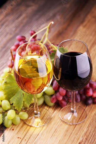 White wine and red wine in a glass with fall grapes on rustic background.