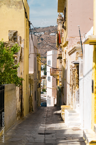 Сozy narrow streets of the old resort European town in a summer sunny day. Low-rise buildings of local residents, small cafes and hotels. Ermoupolis town on Syros island, Cyclades, greece.