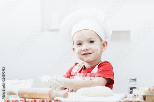 Fotografie, Obraz  Boy with chef hat preparing the pizza dough