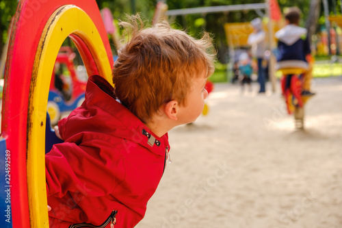 Boy playing on playground carousel in the park