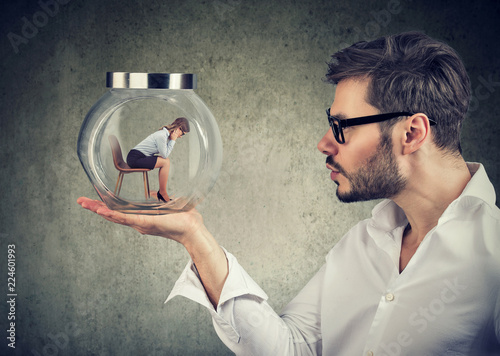Fototapeta Business man holding a glass jar with a young sad business woman trapped in it obraz
