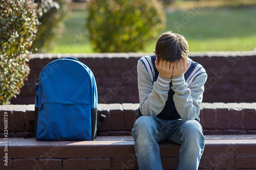 Photo Schoolboy crying in the yard of the school