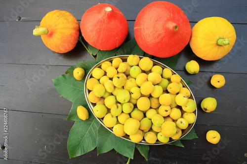 Żółte owoce pigwy w metalowym półmisku na stole, obok kolorowe dynie