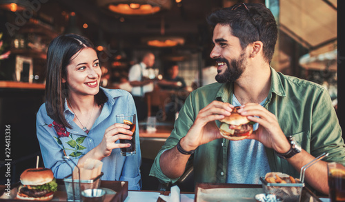 Beautiful young couple sitting in a cafe, having breakfast. Love, dating, food, lifestyle concept
