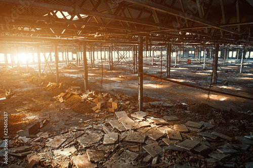 Autocollant pour porte Les vieux bâtiments abandonnés Abandoned, haunted and ruined industrial warehouse or factory building inside in sunlight, large hall with perspective, ruins and demolition concept