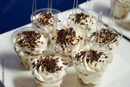 Traditional Tiramisu dessert in a Glass. Chocolate mouse with dark chocolate and a little whipped cream.