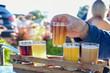 canvas print picture - Man sampling beer at an outdoor beer garden, hands only