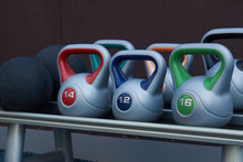 Colorful Kettlebells Weight On Gym Stand, Background. Copy Space. Fitness Sport Equipment