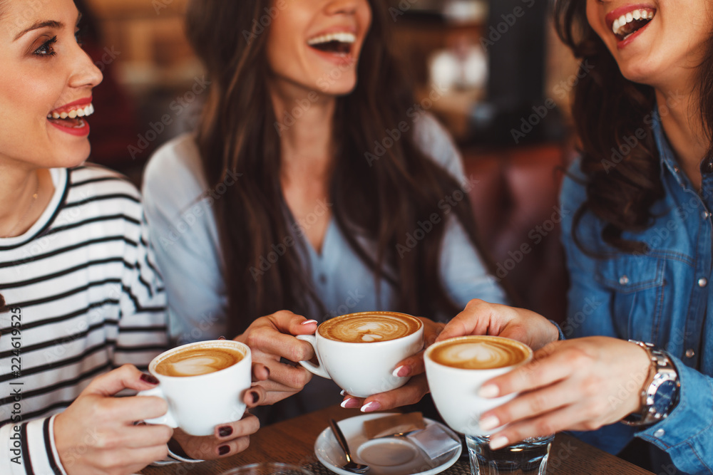 Fototapety, obrazy: Three young women enjoy coffee at a coffee shop