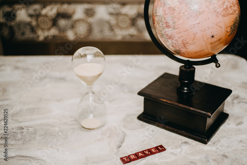 Deurstickers Nasa Globe with the words travel and an hourglass