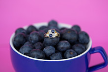 Blue Sapphire And Diamond Gold Ring In A Cup Of Blueberries