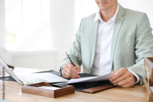 Male notary signing document at table in office, closeup Wallpaper Mural