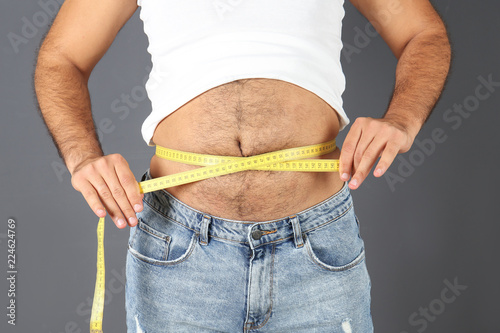 Overweight Man With Measuring Tape On Gray Background
