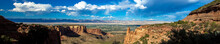 Ultra-wide Panorama Of The Stone Landmarks, Plants, Distant Mountains, And Vast Sky Of Colorado National Monument
