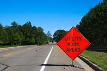 Utility Work Ahead Sign With Service Vehicle Down The Street