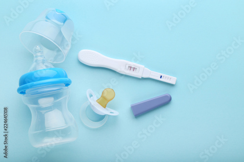 Fototapeta  Pregnancy test with pacifier and little bottle on blue background