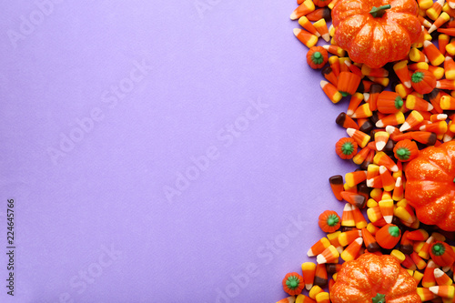 Halloween candy corns and pumpkins on purple background