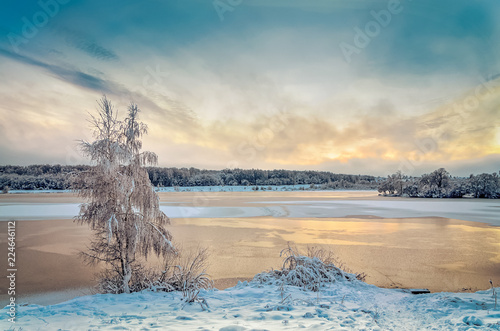 Winter landscape with lake and trees covered with frost
