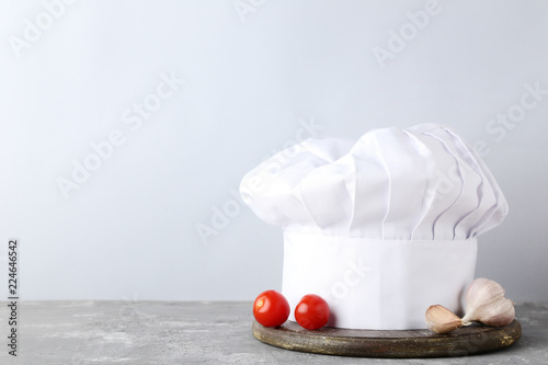 Chef hat with tomatoes and garlic on grey wooden table