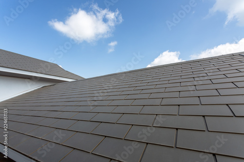 Obraz Slate roof against blue sky, Gray tile roof of construction house with blue sky and cloud background - fototapety do salonu