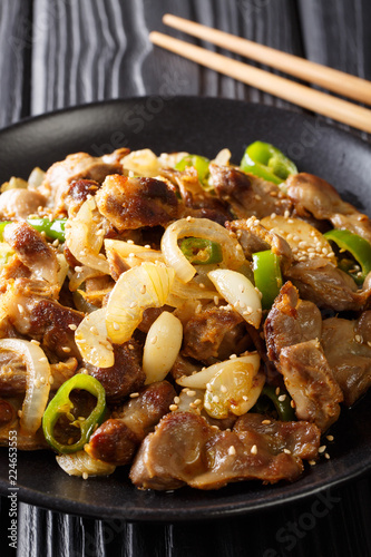 Dak-ttongjip is a Korean dish made by stir-frying chicken gizzard with spices close-up on a plate. vertical