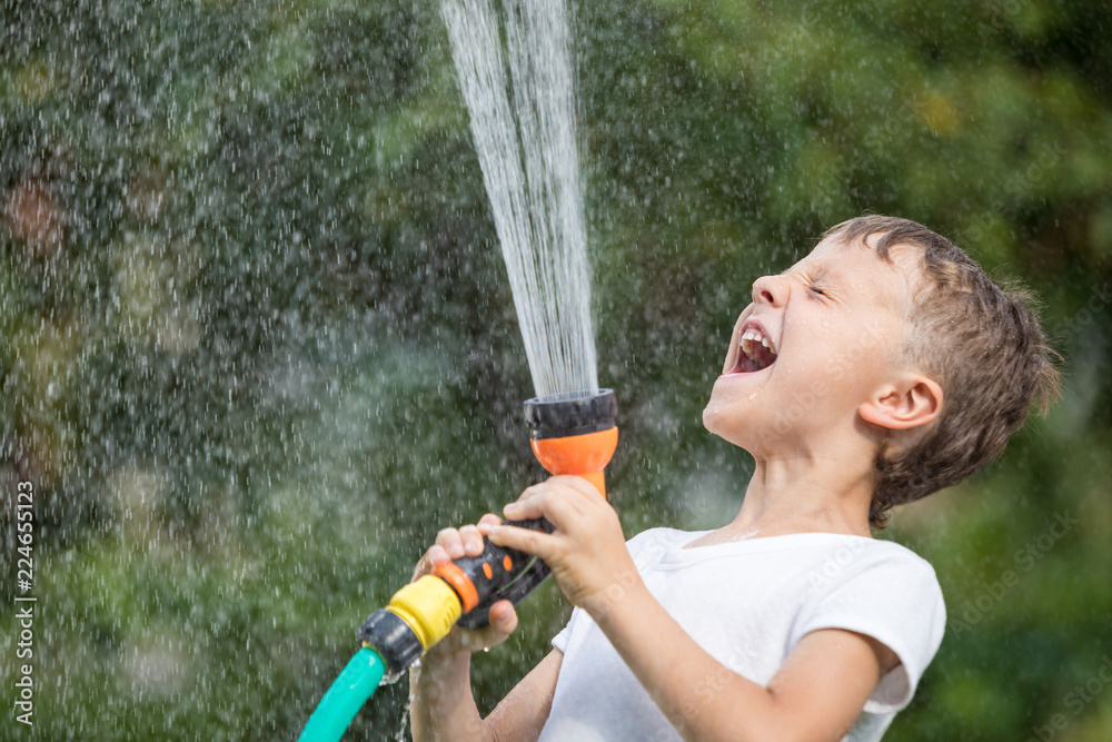 Fototapety, obrazy: Happy little boy pouring water from a hose.