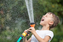 Happy Little Boy Pouring Water...