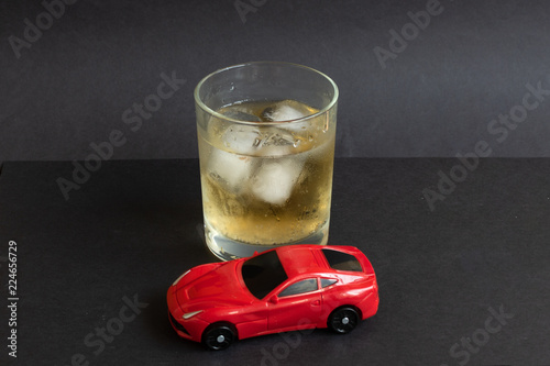Foto op Aluminium Bar Alcohol and car toy on color background. Driving in a drunken state concept.