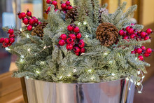 Christmas Bouquet Composition With Tree Branches, Pine Cone And Red Berries In Metal Basket