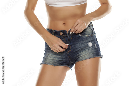 Fotografía  A young woman unzipping her short jeans on white background