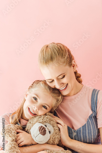 beautiful happy mother and daughter with teddy bear isolated on pink