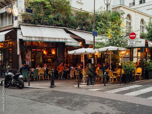 Fototapeta premium Przytulna ulica z stołami kawiarni w Paryżu, Francja