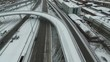 Brown car riding on motorway. Almost alone. Aerial view of snowy day with snowy motorway.