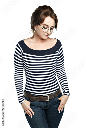 914379b3 Young attractive eastern with round glasses in a striped tight blouse,  hands in pockets. Isolated on white background. Looks down.