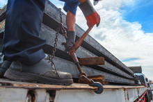 Workers Driver Of The Trailer Lorry Is Lashing Securing Steel Slab On The Trailer, Lashing Securing Goods By Tightening Chain For Lashing Before Delivery To9 The Destination