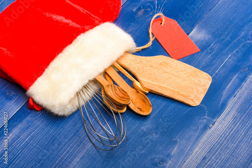 Fotografía  Kitchen accessories for cooking or kit of kitchenware packed in big red sock on wooden blue background