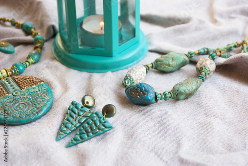 Indian bohemian style jewelry with tuquoise gold necklace and earrings. Fashion jewelry. Turquoise color background.