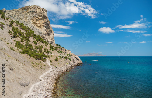 Foto op Canvas Kust Blue sea with the rocky shore in the sunny afternoon