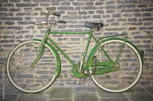 Fototapety, obrazy: Old green bicycle parked against a brick wall