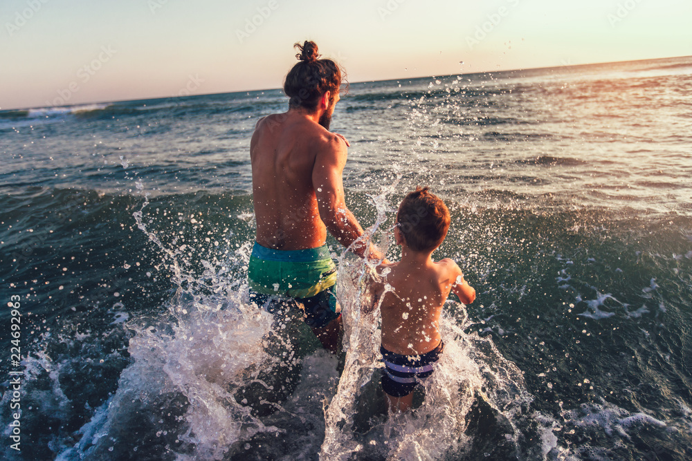 Fototapety, obrazy: Father and son playing on the beach at the day time