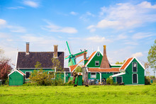 Dutch Typical Landscape. Traditional Old Dutch Windmill With Old Houses Against Blue Cloudy Sky In The Zaanse Schans Village, Netherlands. Famous Tourism Place. Sheep Grazing On Green Grass.