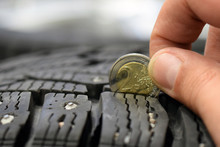 Measuring Tire Tread Depth With Two Euro Coin. Close Up Image With Room For Text. Shallow Depth Of Field.