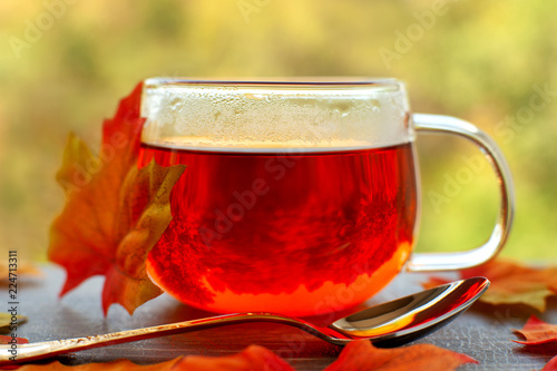 Hot tea for cold autumn. A cup of hot tea, a maple leaf and a dessert spoon on the windowsill. Hot tea in the background of a window and autumn nature.