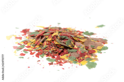 closeup of various flakes on goldfish food on white background