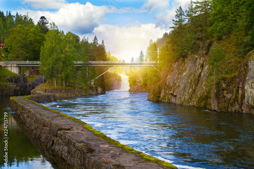 Bridge above the river and waterfall. View of the Telemark Canal with old locks - tourist attraction in Skien, Norway