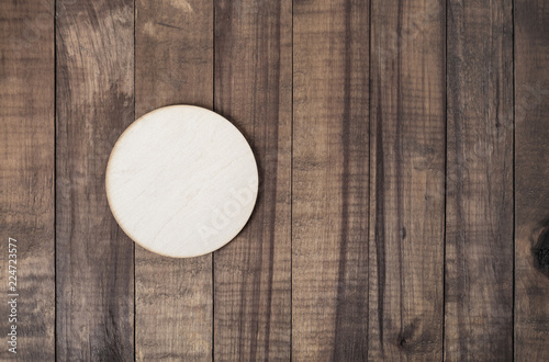Blank wooden beer coaster on wood table background. Responsive design mockup. Flat lay.