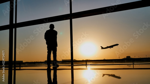 Photo  Silhouette of a tourist guy watching the take-off of the plane standing at the airport window at sunset in the evening