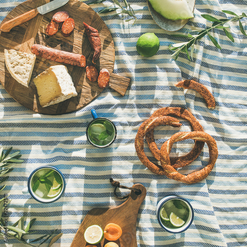 Flat-lay of summer picnic set with fruit, cheese, sausage, bagels and lemonade over striped blanket, top view, square crop