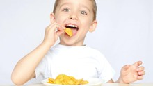 A Child With Pleasure Eating Potato Chips Sitting At A Table On A White Background. The Boy Is Eating Chips And Smiling.
