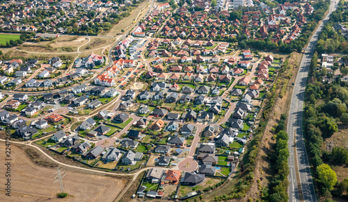 Fototapeta Aerial view of a German suburb with streets and many small houses for families, photographed by a gyrocopter. obraz na płótnie
